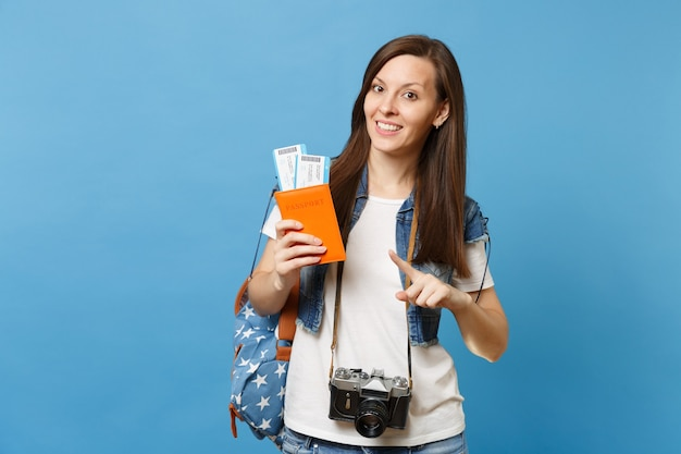 Młoda ładna kobieta studentka z retro vintage aparat fotograficzny na szyi, wskazując palcem wskazującym w paszporcie, bilety na pokład na białym tle na niebieskim tle. edukacja na studiach za granicą. lot w podróży lotniczej.
