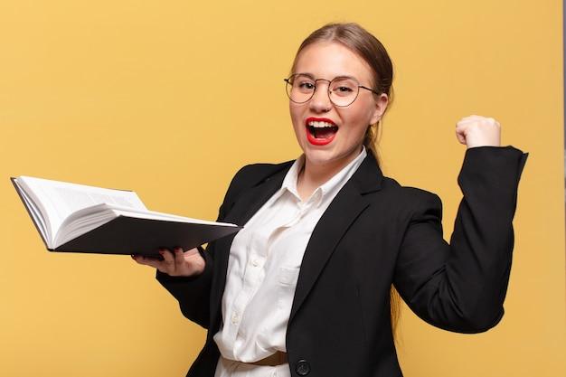 Młoda ładna kobieta świętuje koncepcję biznesową sukcesu