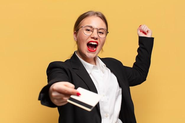 Młoda ładna kobieta. świętujemy triumf niczym zwycięska koncepcja karty kredytowej