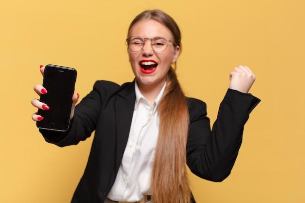 Młoda ładna kobieta. świętujemy triumf niczym zwycięska koncepcja smartfona