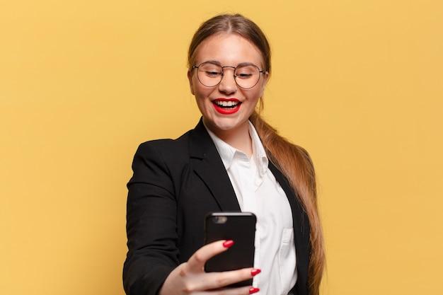 Młoda ładna kobieta szczęśliwa i zdziwiona koncepcja inteligentnego telefonu wyrażenie