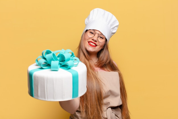 Młoda ładna kobieta. szczęśliwa i zdziwiona koncepcja tort urodzinowy z wyrażeniem