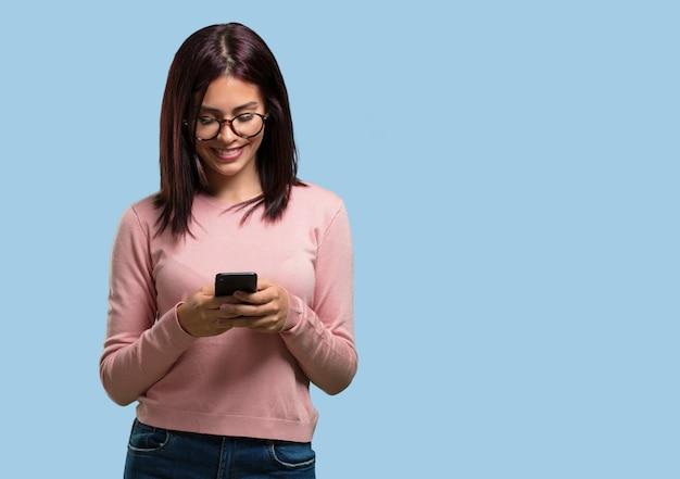 Młoda ładna kobieta szczęśliwa i zrelaksowana, dotykając telefonu komórkowego, korzystając z internetu i sieci społecznościowych