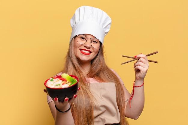 Młoda ładna kobieta. szczęśliwy i zaskoczony wyraz twarzy. koncepcja gotowania makaronu szefa kuchni