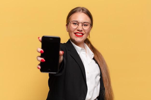 Młoda ładna kobieta. szczęśliwy i zaskoczony wyraz twarzy. koncepcja inteligentnego telefonu