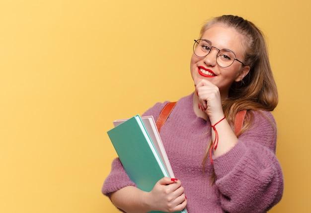 Młoda ładna kobieta. szczęśliwy i zaskoczony wyraz twarzy. koncepcja studenta