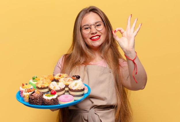 Młoda ładna kobieta. szczęśliwy i zdziwiony piekarz z babeczkami