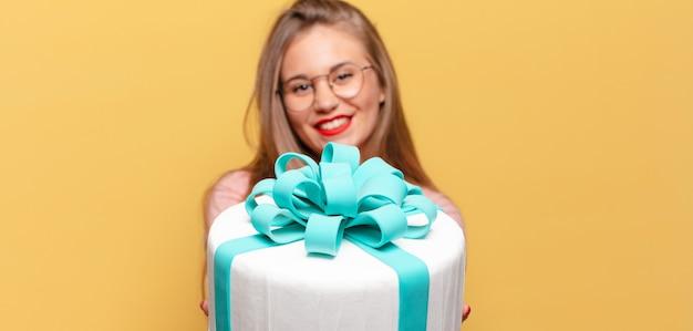 Młoda ładna kobieta. szczęśliwy i zdziwiony wyrażenie koncepcja tort urodzinowy