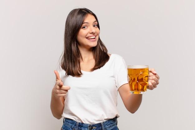 Młoda ładna kobieta szczęśliwy wyraz i trzyma piwo