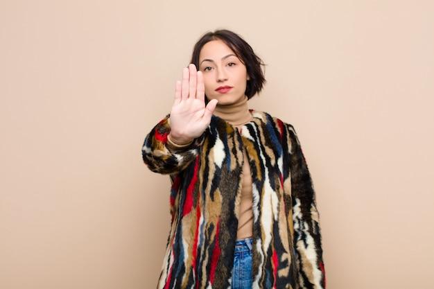Młoda ładna kobieta szuka poważnego, surowego, niezadowolonego i gniewnego seansu otwartej dłoni robi przerwie gestykuluje przeciw beż ścianie