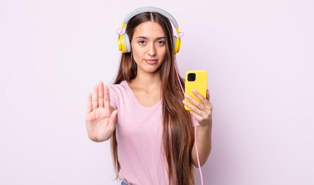 Młoda ładna kobieta szuka poważnego wyświetlono otwartej dłoni dokonywanie gest zatrzymania. słuchawki i smartfon