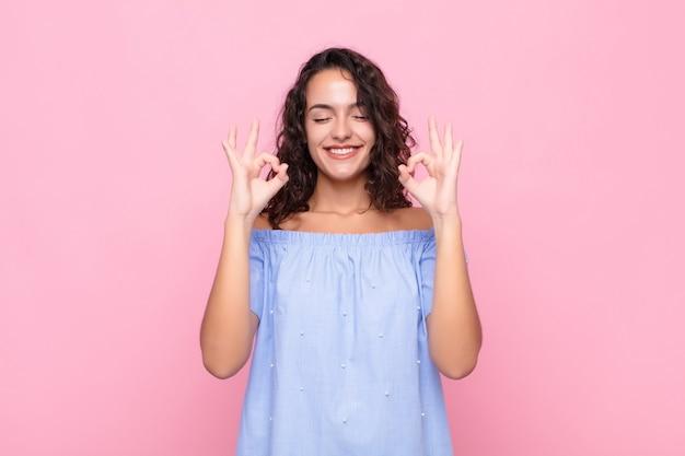 Młoda ładna kobieta szuka skoncentrowanej i medytacji, czuje się usatysfakcjonowana i zrelaksowana, myśli lub dokonuje wyboru ponad różową ścianą