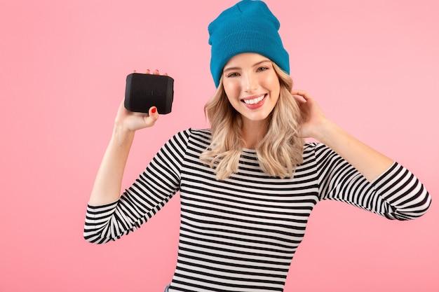 Młoda ładna kobieta trzyma głośnik bezprzewodowy słuchający muzyki w pasiastej koszuli i niebieskim kapeluszu, uśmiechając się szczęśliwy pozytywny nastrój pozuje na różowym tle