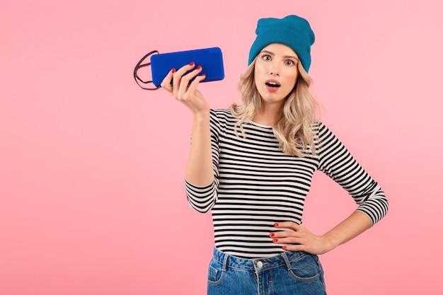 Młoda ładna kobieta trzyma głośnik bezprzewodowy słuchanie muzyki na sobie koszulę w paski i niebieski kapelusz uśmiechnięty szczęśliwy pozytywny nastrój pozowanie na różowej ścianie na białym tle