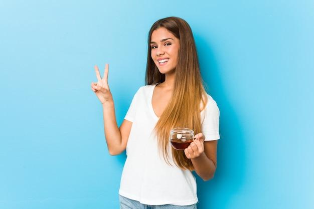 Młoda ładna kobieta trzyma herbacianą filiżankę radosną i beztroską pokazuje symbol pokoju z palcami