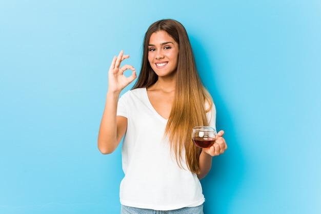 Młoda ładna kobieta trzyma herbacianą filiżankę rozochoconą i ufną pokazuje ok gest.