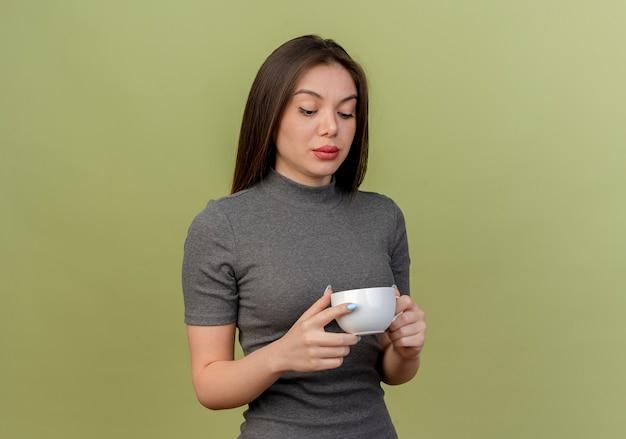 Młoda ładna kobieta trzyma i patrząc na kubek na białym tle oliwkowej z miejsca kopiowania