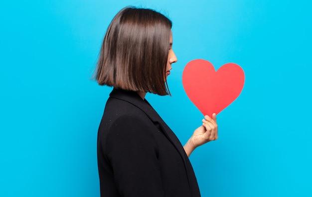 Młoda ładna kobieta trzyma kartę serca
