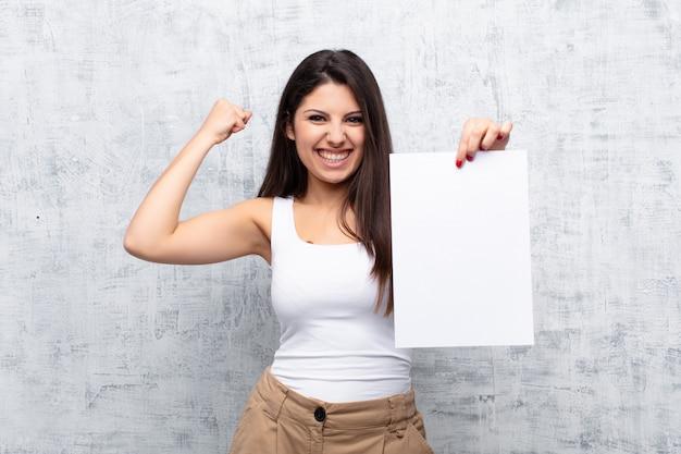 Młoda ładna kobieta trzyma kartkę papieru przed ścianą cementu grunge