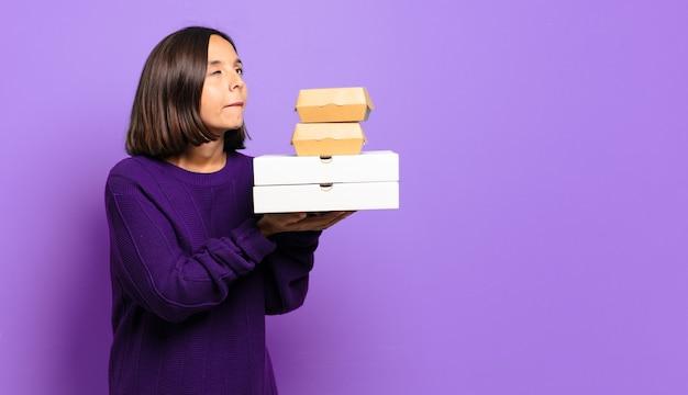 Młoda ładna kobieta trzyma na wynos pudełka z fast foodami