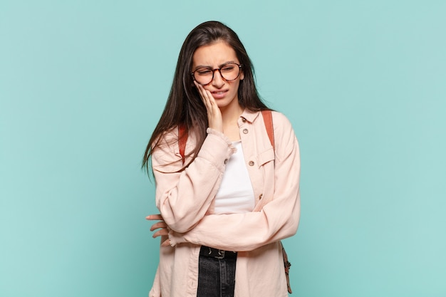 Młoda ładna kobieta trzyma policzek i cierpi na bolesny ból zęba, czuje się chora, nieszczęśliwa i nieszczęśliwa, szuka dentysty. koncepcja studenta