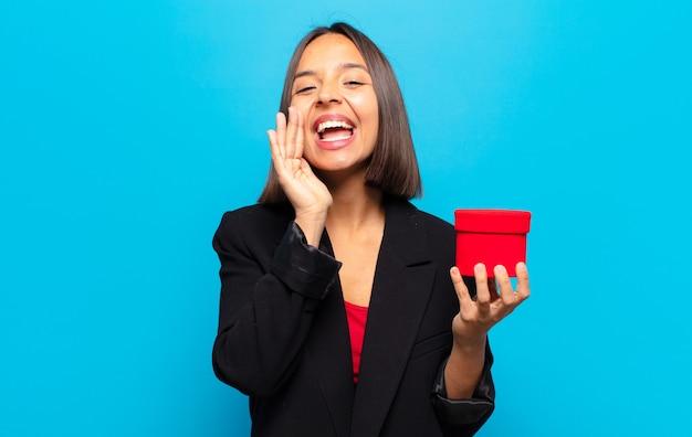 Młoda ładna kobieta trzyma pudełko na prezent