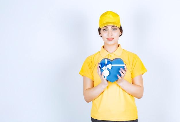 Młoda ładna kobieta trzyma pudełko w kształcie serca na białej ścianie