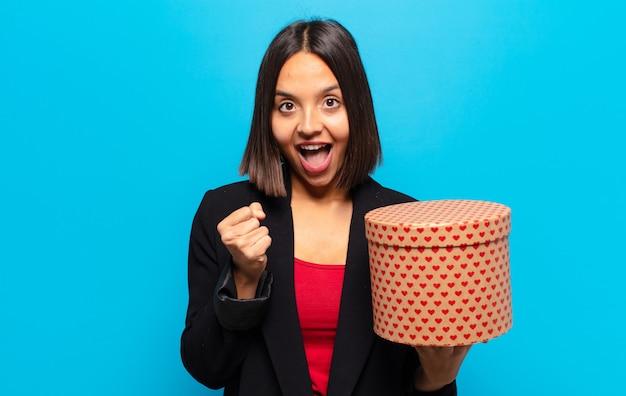 Młoda ładna kobieta trzyma pudełko