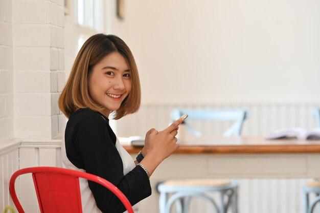 Młoda ładna kobieta trzyma smartphone