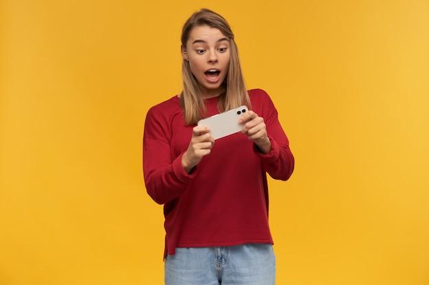 Młoda ładna kobieta trzyma w rękach telefon komórkowy, patrzy na niego z podekscytowaniem, otwiera usta, wstrzymuje oddech, jakby grała w ekscytującą grę