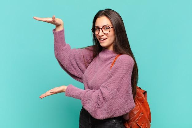 Młoda ładna kobieta trzymająca przedmiot obiema rękami na bocznej przestrzeni kopii, pokazująca, oferująca lub reklamująca przedmiot. koncepcja studenta