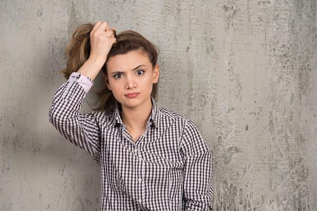 Młoda ładna kobieta trzymająca włosy w kucyk