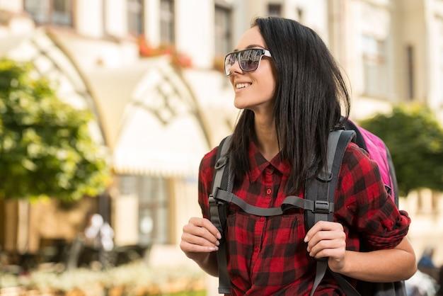 Młoda ładna kobieta, turysta z plecakiem, ono uśmiecha się.