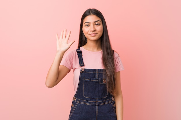 Młoda ładna kobieta ubrana w dżinsy ogrodniczki uśmiechający się wesoły pokazano numer pięć palcami