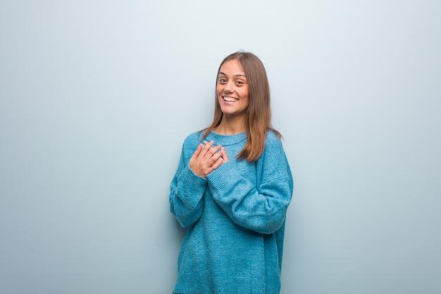 Młoda ładna kobieta ubrana w niebieski sweter robi romantyczny gest