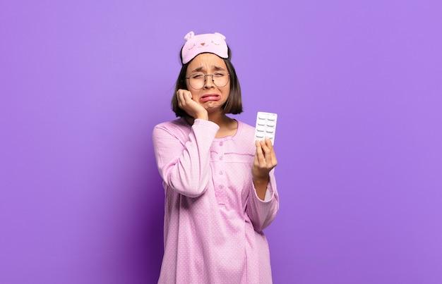 Młoda ładna kobieta ubrana w piżamę i trzymająca pigułki