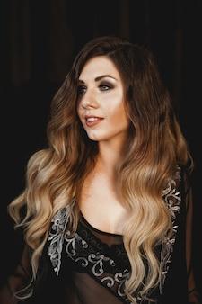 Młoda ładna kobieta, ubrana w przezroczysty czarny szlafrok peniuar w ciemnym pokoju