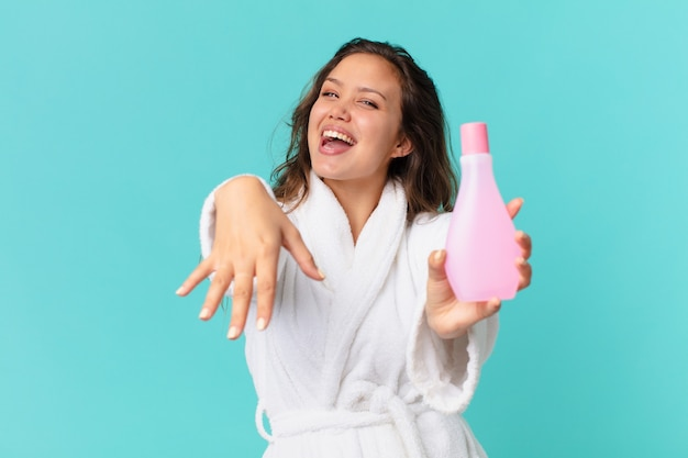 Młoda ładna kobieta ubrana w szlafrok i trzymająca czystą butelkę produktu