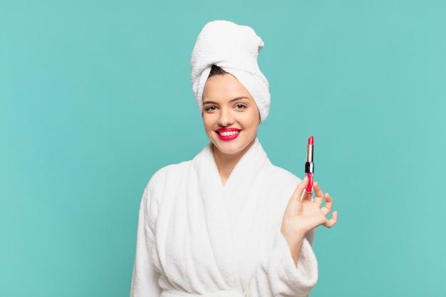 Młoda ładna kobieta ubrana w szlafrok szczęśliwy wyraz twarzy i szminkę