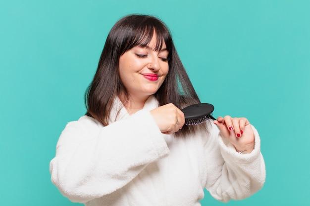 Młoda ładna kobieta ubrana w szlafrok szczęśliwy wyraz twarzy i trzymająca szczotkę do włosów