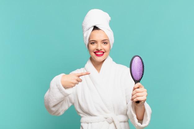 Młoda ładna kobieta ubrana w szlafrok wskazujący lub pokazująca i trzymająca szczotkę do włosów