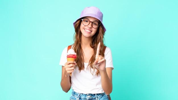 Młoda ładna kobieta uśmiecha się dumnie i pewnie co numer jeden, trzymając lody. koncepcja lato