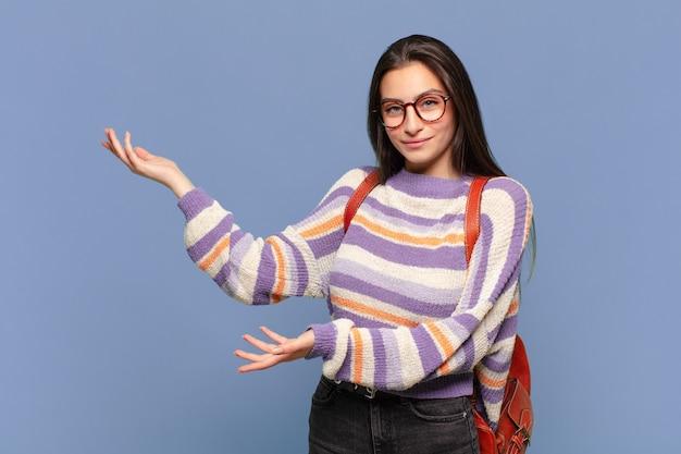 Młoda ładna kobieta uśmiecha się dumnie i pewnie, czuje się szczęśliwa i usatysfakcjonowana, i pokazuje koncepcję na przestrzeni kopii