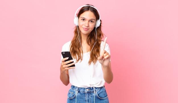 Młoda ładna kobieta uśmiecha się dumnie i pewnie robi numer jeden ze słuchawkami i smartfonem