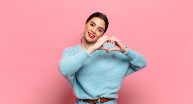 Młoda ładna kobieta uśmiecha się i czuje się szczęśliwa, urocza, romantyczna i zakochana, tworząc kształt serca obiema rękami