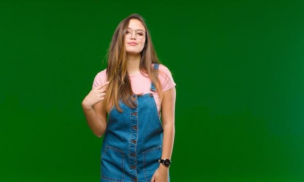Młoda ładna kobieta uśmiecha się i niespokojnie ścina oba palce, czuje się zmartwiona i marzy lub ma nadzieję na szczęście na zielonej ścianie