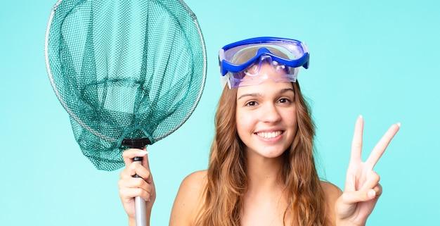 Młoda ładna kobieta uśmiecha się i wygląda na szczęśliwą, gestykulując zwycięstwo lub pokój za pomocą okularów i sieci rybackiej