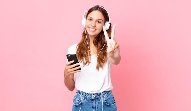 Młoda ładna kobieta uśmiecha się i wygląda na szczęśliwą, gestykulując zwycięstwo lub pokój za pomocą słuchawek i smartfona