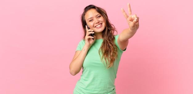 Młoda ładna kobieta uśmiecha się i wygląda na szczęśliwą, gestykuluje zwycięstwo lub pokój i trzyma smartfona