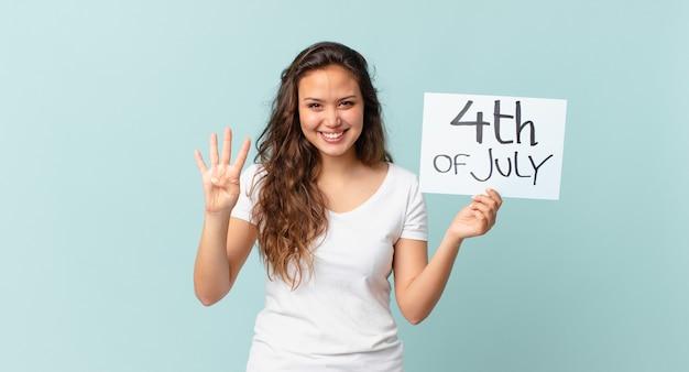 Młoda ładna kobieta uśmiecha się i wygląda przyjaźnie, pokazując koncepcję dnia niepodległości numer cztery